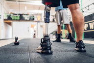 Man with prosthetic leg and friend in gym - CUF50385