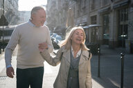 Senior couple laughing on street in city - CUF50415
