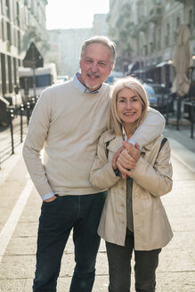 Senior couple hugging on street in city - CUF50418