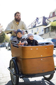 Happy father with two children riding cargo bike in the city - MAEF12833