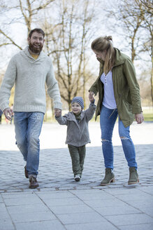 Happy parents walking hand in hand with son - MAEF12836