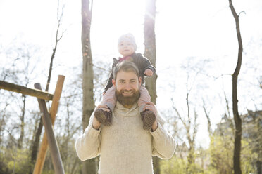Portrait of happy father carrying daughter on shoulders in park - MAEF12842