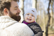 Happy father carrying daughter in park - MAEF12845