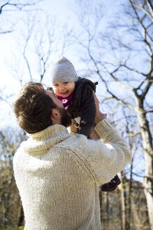 Father lifting up happy daughter in park - MAEF12848