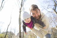 Portrait of happy father holding daughter in park - MAEF12851