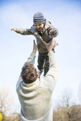 Father throwing happy boy in the air under blue sky - MAEF12854