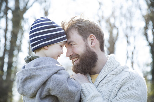 Happy father carrying son in park - MAEF12857