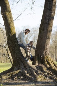 Father playing with son at a tree in park - MAEF12860