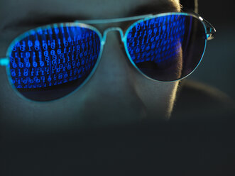 Cyber Crime, reflection in spectacles of virus hacking a computer, close up of face - ABRF00369