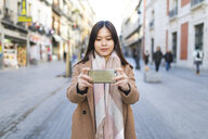 Spain, Madrid, young woman taking photos with a smartphone in the city - WPEF01469