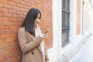 Young woman using cell phone at brick wall - WPEF01472
