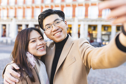 Spain, Madrid, happy young couple taking a selfie in the city - WPEF01478