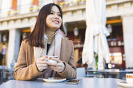 Spain, Madrid, smiling young woman in a cafe at Plaza Mayor - WPEF01493