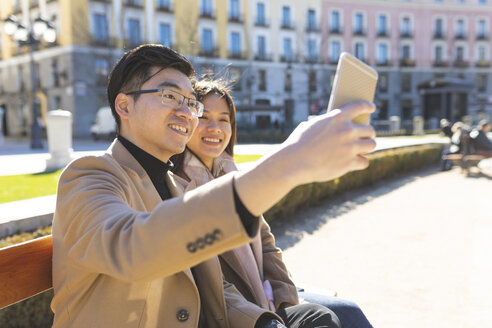 Spain, Madrid, young couple resting on a bench and taking a selfie in the city - WPEF01499