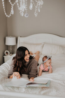 Mother reading with baby daughter on bed in bedroom - ISF21132