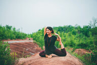 Woman doing pigeon pose on rock - ISF21150