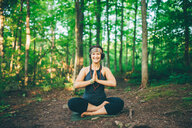 Woman doing prayer pose in forest - ISF21153