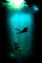 Underwater view of male and female scuba divers exploring cenote called the pit, Tulum, Quintana Roo, Mexico - ISF21174
