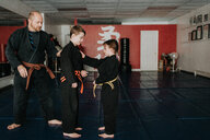 Coach and students practising martial arts in studio - ISF21198