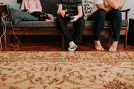 Mother sitting with children playing video game on couch - ISF21213