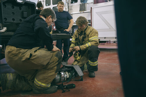 Firefighters checking equipment in fire station - HEROF35556