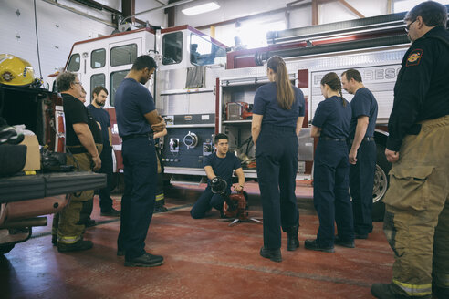 Firefighters meeting, checking equipment at fire engine at fire station - HEROF35562