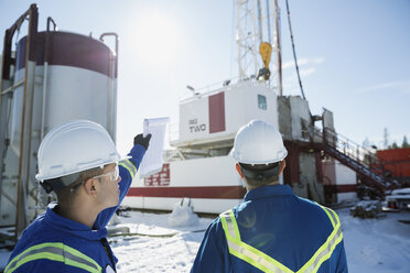 Male workers pointing up drilling rig in snow - HEROF35604