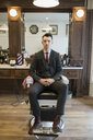 Portrait confident barber wearing suit barber shop chair - HEROF35625