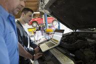 Mechanics with laptop performing engine diagnostics - HEROF35640