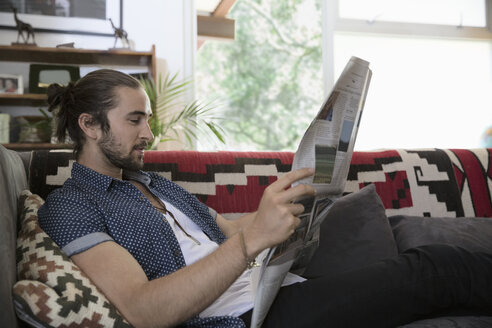 Man reading newspaper on living room sofa - HEROF35655