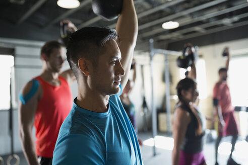 Man weightlifting kettlebell crossfit exercise class - HEROF35694