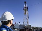 Male worker looking up drilling rig blue sky - HEROF35706