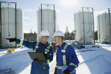 Male engineers using laptop at snowy gas plant - HEROF35718