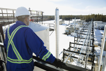 Male worker on platform overlooking gas plant - HEROF35721