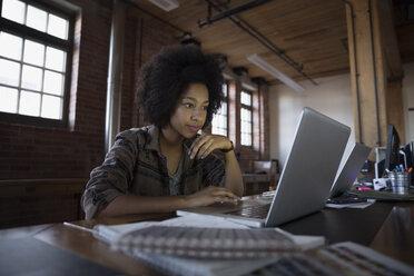 Focus designer working a laptop in office - HEROF35730