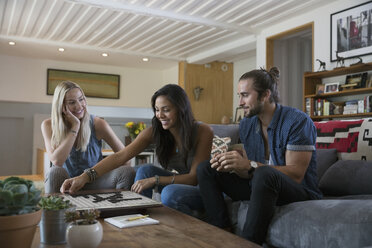 Friends playing board game in living room - HEROF35784