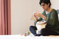 Woman embroidering sitting on bed at home - IGGF01022