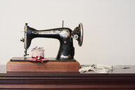 Old vintage sewing machine with measuring tape and pin chusion in shape of a hat - IGGF01025