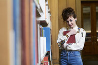 Female student holding a book in a public library - IGGF01052