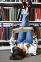 Female student reading book in a public library - IGGF01058