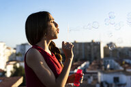 Teenage girl blowing soap bubbles on roof terrace in the city at sunset - ERRF00938