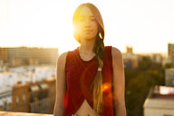 Portrait of teenage girl on roof terrace in the city at sunset - ERRF00947