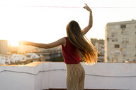 Rear view of gracious teenage girl moving on roof terrace in the city at sunset - ERRF00956