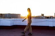 Teenage girl walking on roof terrace in the city at sunset - ERRF00962