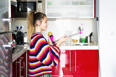 Girl playing with microphone and smartphone in kitchen at home - ERRF00995