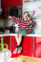 Girl playing with microphone and smartphone in kitchen at home - ERRF00998