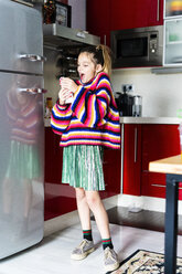 Excited girl in striped pullover in kitchen at home eating chocolate - ERRF01001