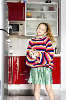 Girl in striped pullover in kitchen at home eating chocolate - ERRF01004