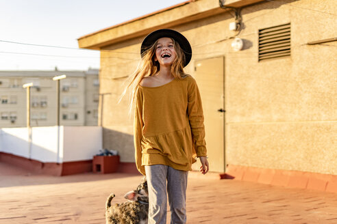 Portrait of laughing girl on roof terrace with her dog - ERRF01013