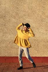 Happy girl wearing oversized hat dancing on root terrace - ERRF01016